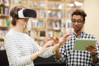 Two teens use augmented reality at a library
